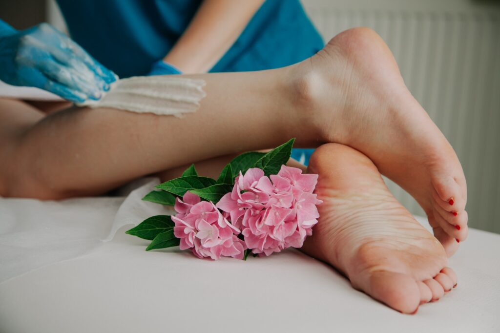 Sugaring master putting epilation wax paste on the legs. Depilation concept. Epilation wax concept.